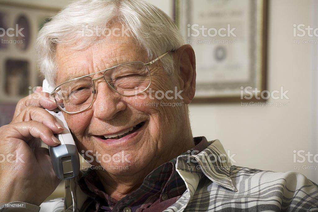senior man smiling and talking on telephone royalty-free stock photo