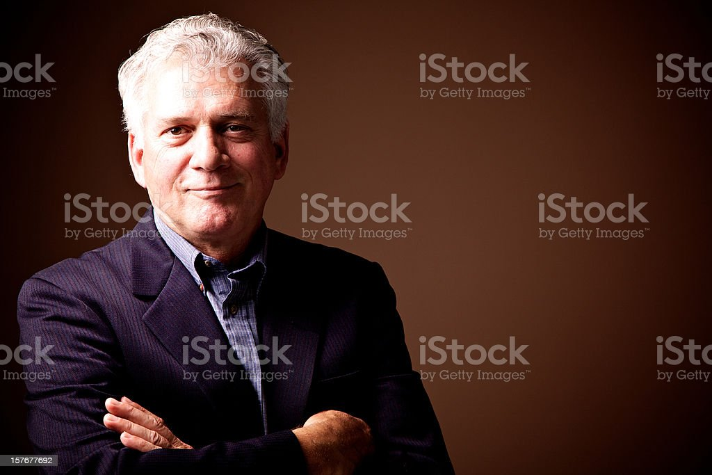 Senior man smiling, armscrossed, looking at the camera stock photo