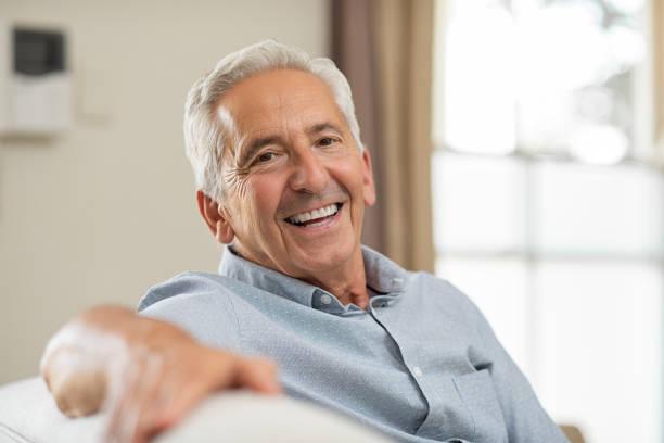 älterer mann lächelnd zu hause fühlen - einzelner senior stock-fotos und bilder