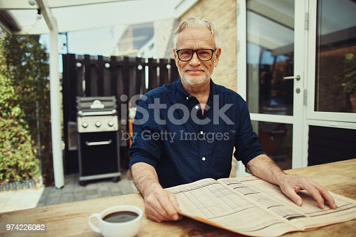116379055 istock photo Senior man smiling contently while sitting outside reading a newspaper 974226082