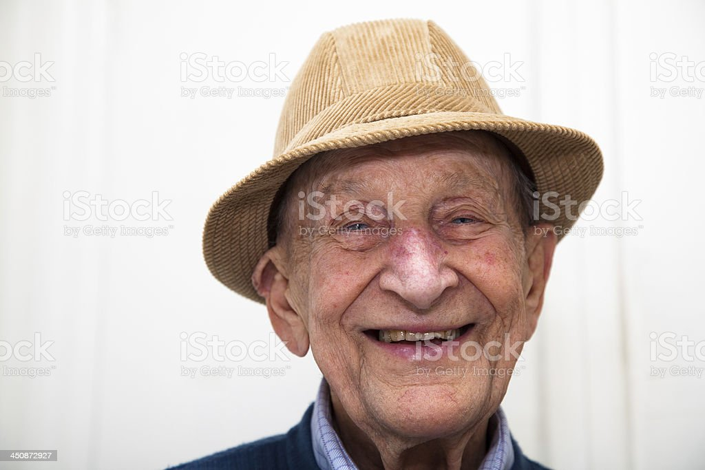 Senior man smiling in a corduroy hat stock photo