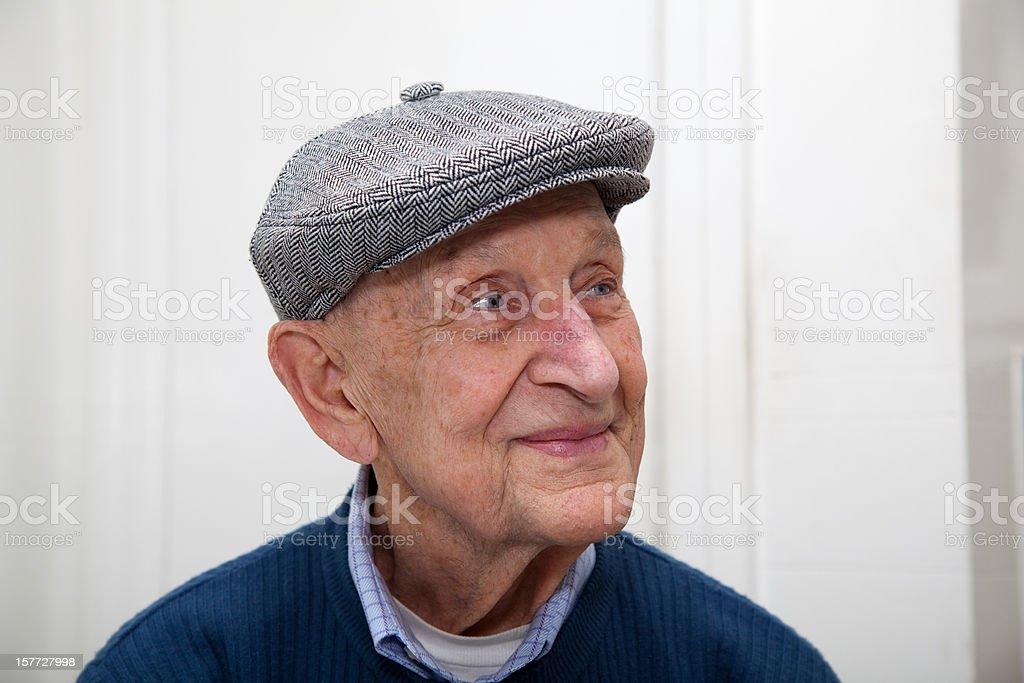 Älterer Mann lächelnd mit grauer herringbone-Schiebermütze - Lizenzfrei 90 und älter Stock-Foto