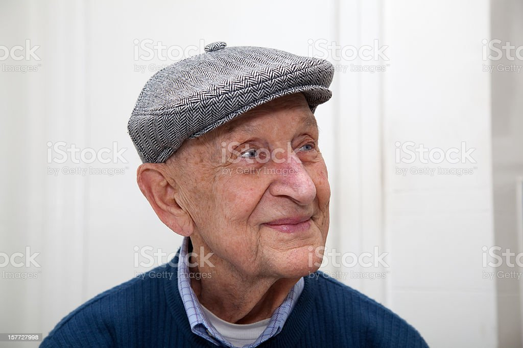 Senior man smiling with grey herringbone flat cap stock photo
