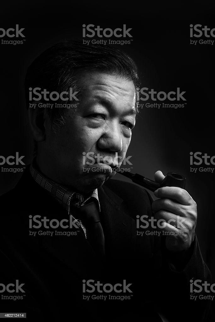 Senior man smoking a pipe stock photo