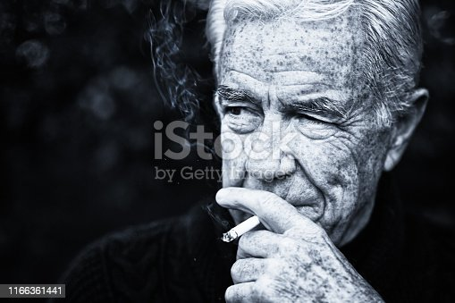 A wrinkled senior man looks sideways as he smokes a cigarette in this monochrome image.