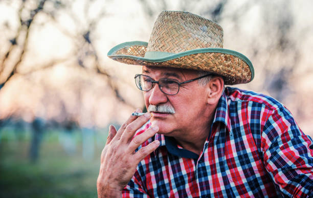 Senior man smoking cigarette stock photo