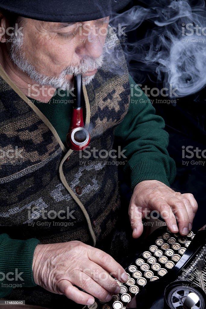 senior man smoking pipe with looking vintage typewriter royalty-free stock photo