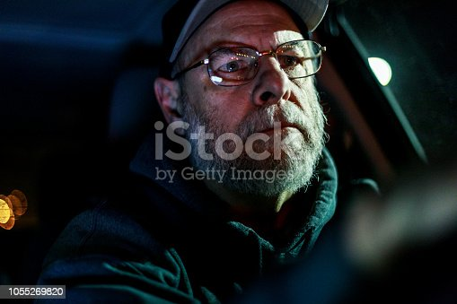 A senior adult man on a night road trip journey is driving his car alone just after midnight. It's winter in December and he's wearing a warm hoody-type hooded sweatshirt and a baseball cap as he looks forward, concentrating on the road ahead.