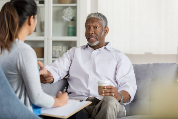 Senior man speaks openly with attentive therapist A senior man sits on a couch opposite his unrecognizable female therapist and gestures as he shares openly with her.  His therapist holds a pen and clipboard ready to take notes. psychotherapy stock pictures, royalty-free photos & images
