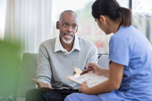 senior man speaks with home health nurse - visita foto e immagini stock