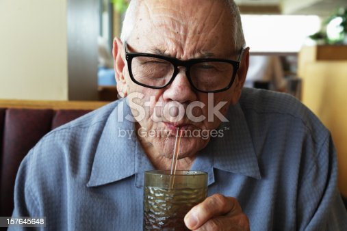 A senior man sitting in a diner-style restaurant squints as he drinks from a water glass through a straw. Selective focus on his face.