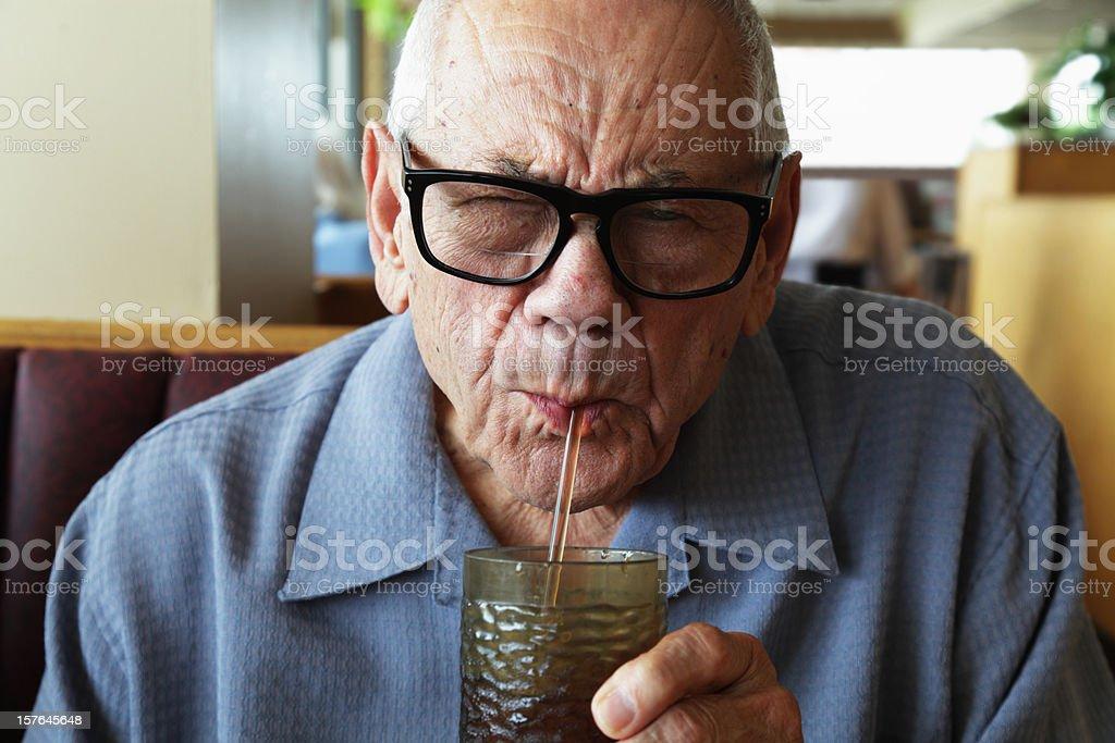 Senior Man Squinting While Drinking Water Through Straw stock photo