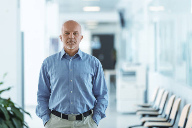 senior man standing and facing the camera with hands in pocket stock photo