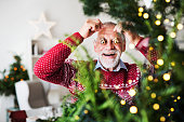A cheerful senior man standing by Christmas tree, putting balls in front of his eyes.