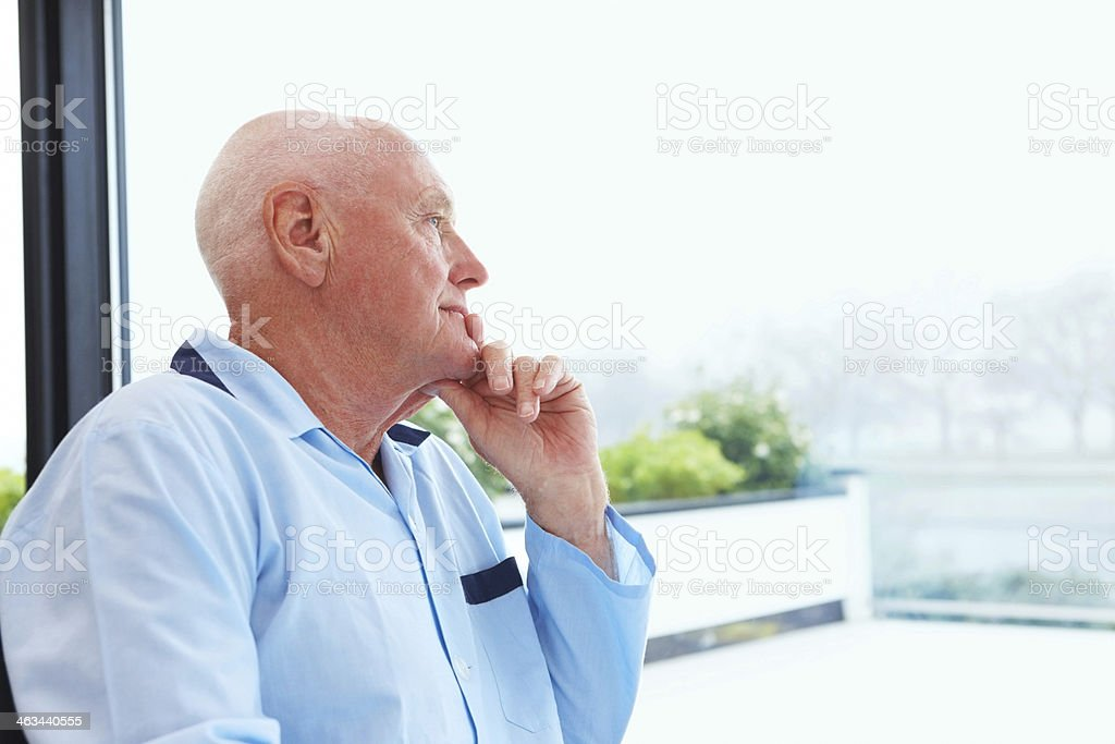 Senior man standing by window looking outside stock photo