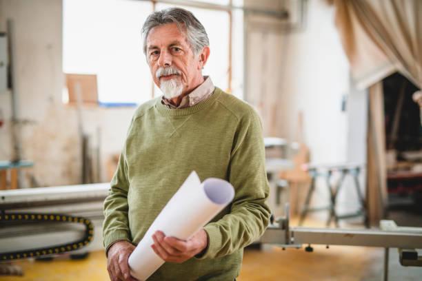Seniorenmensch steht in einer Werkstatt und hält eine Blaupause in den Händen – Foto