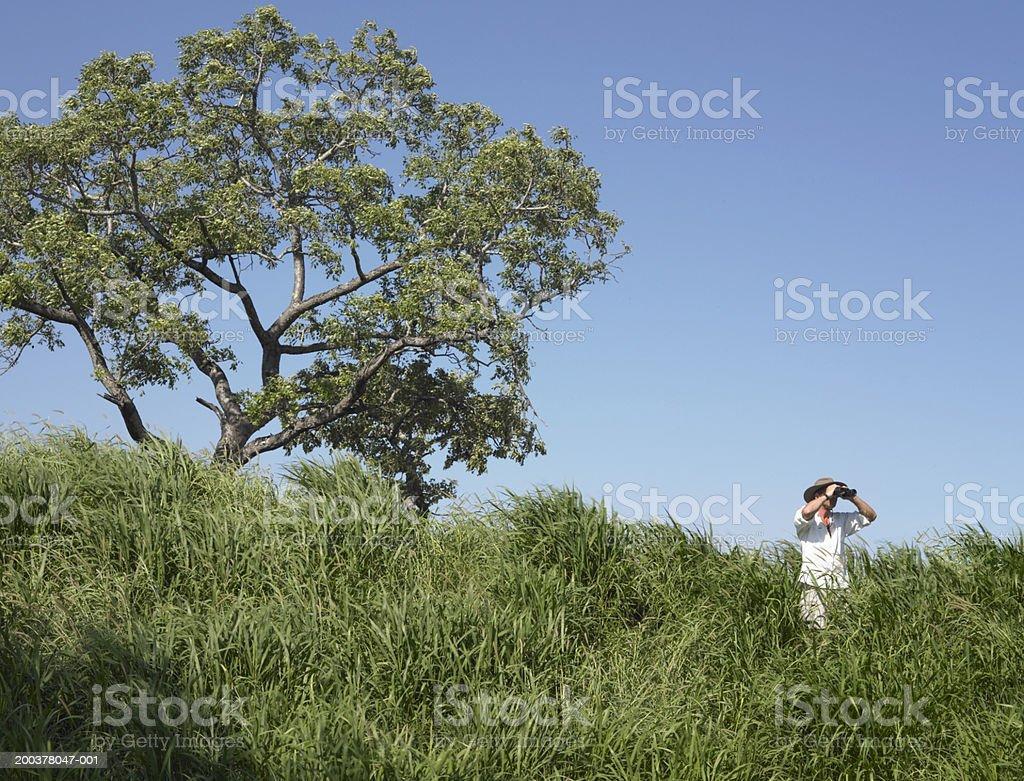 Senior man standing in long grass using binoculars royalty-free stock photo