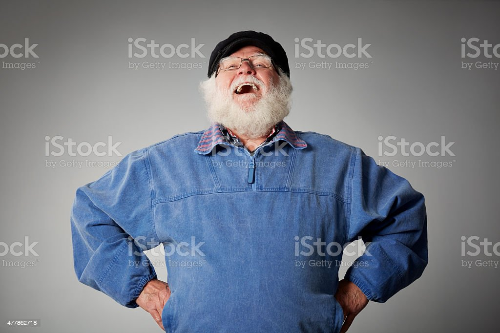 Senior man standing laughing against grey background stock photo