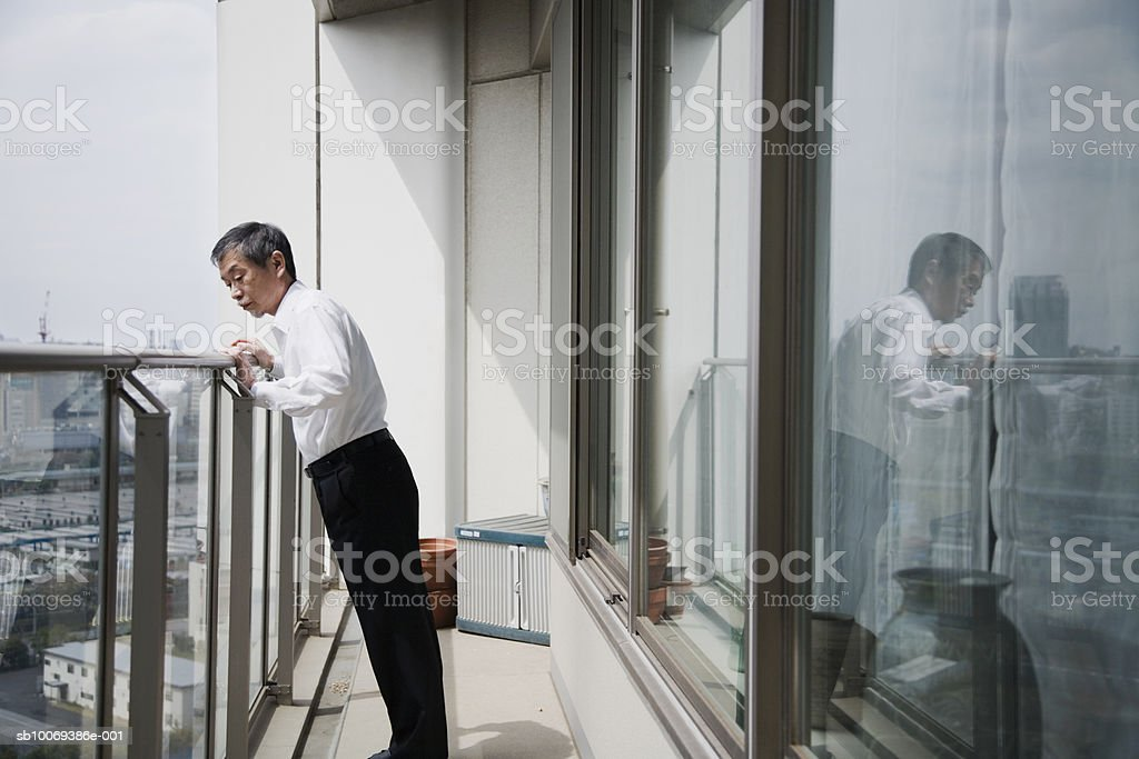 Senior man standing on balcony looking down royalty-free 스톡 사진