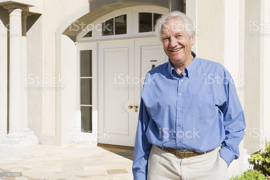 Senior man standing outside house royalty-free stock photo