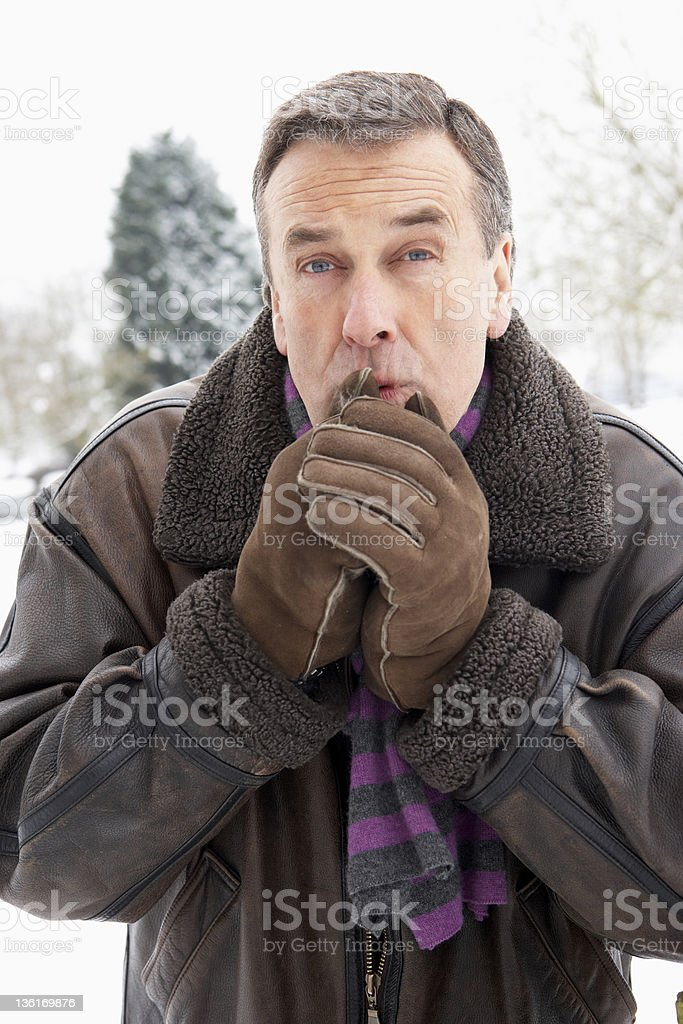 Senior Man Standing Outside In Snowy Landscape Warming Hands royalty-free stock photo