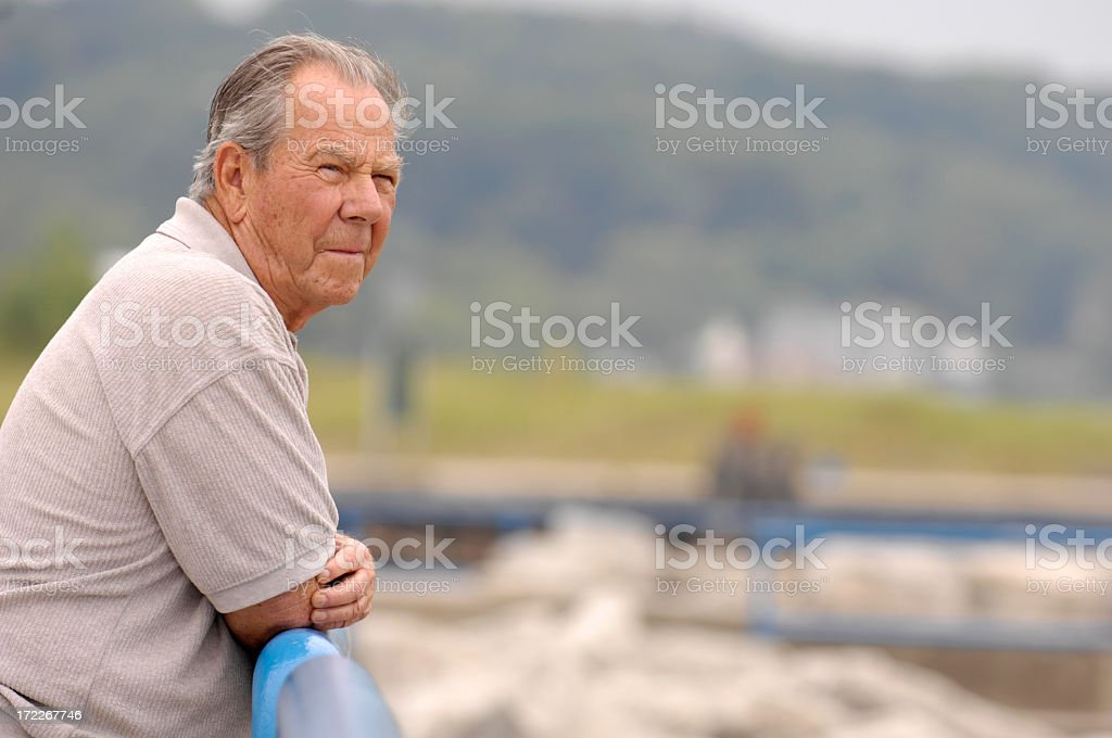 Senior man standing over a railing at a port royalty-free stock photo