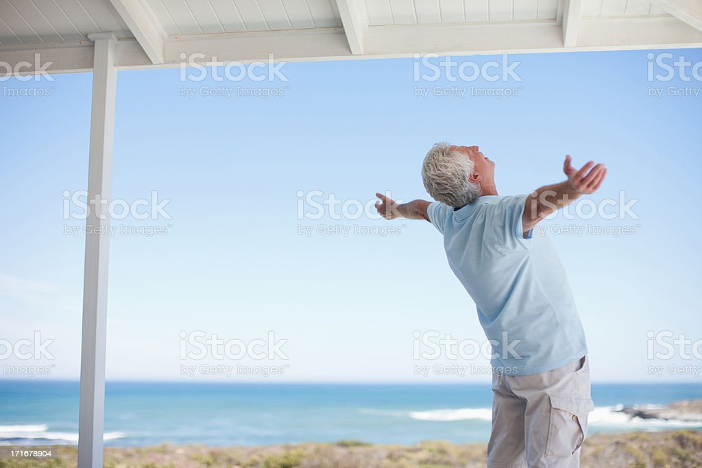 Senior man standing with arms outstretched stock photo