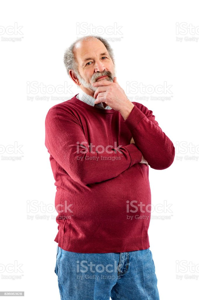 Senior man standing with his hand on chin stock photo