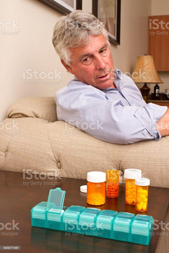 Senior Man Stares at Medications stock photo