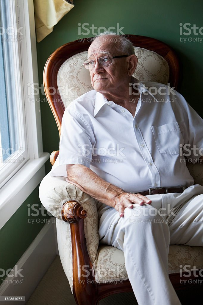 Senior man staring out a window stock photo