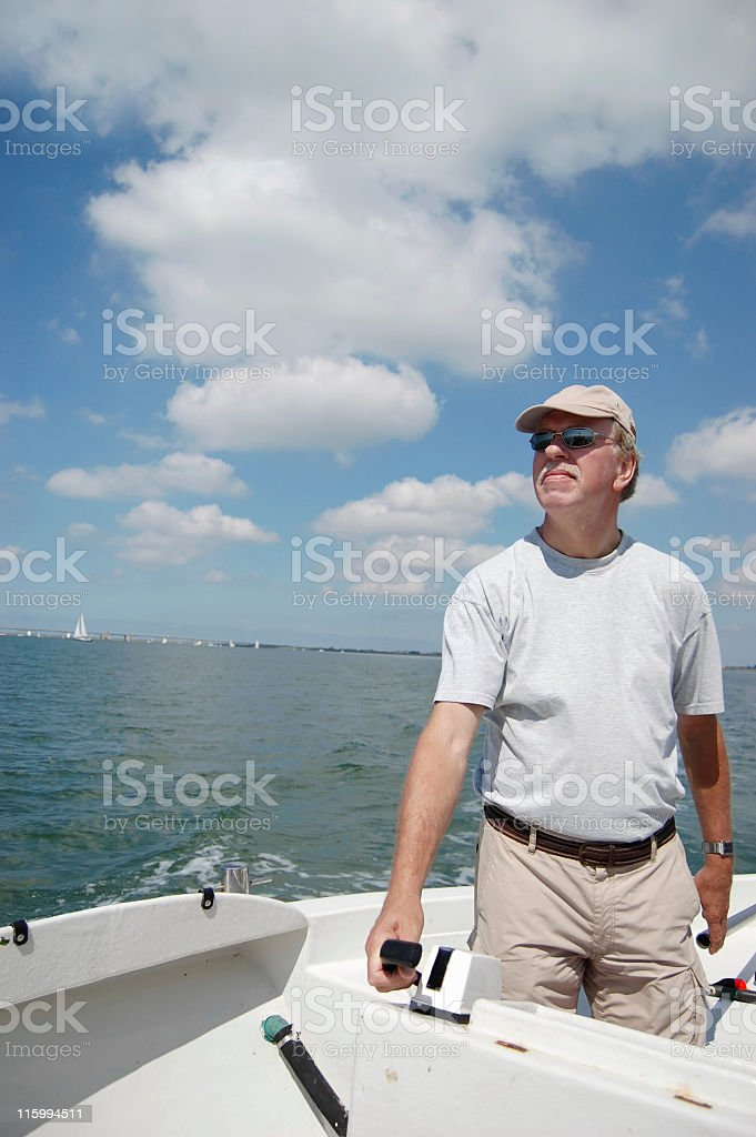 Senior man steering motorboat on Eastern Scheldt,Zeeland,the Netherlands royalty-free stock photo