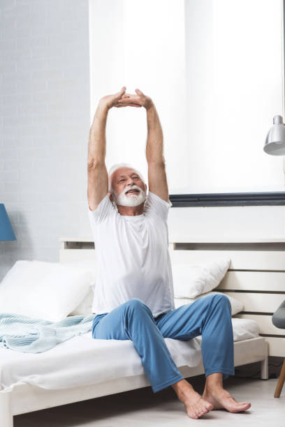 Senior man stretch on bed in morning stock photo