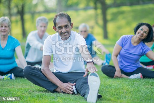 646614234 istock photo Senior Man Stretches With Group 801309754