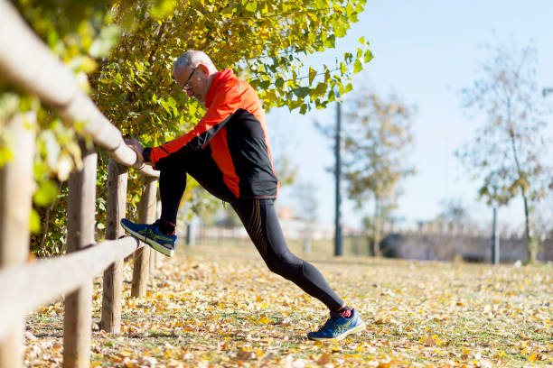 senior man stretching after jogging in the park - old man feet stock photos and pictures