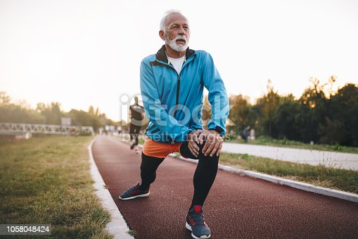 Senior bearded man jogging on a running track outdoors, in a tracksuit.
