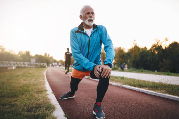Senior man stretching while jogging on a running track Senior bearded man jogging on a running track outdoors, in a tracksuit. young at heart stock pictures, royalty-free photos & images
