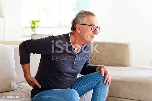Worried senior man sitting on sofa at home and touching his back. Elderly man suffering lumbar spine.