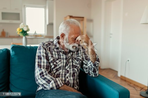 A Distraught Senior Man Suffering From a Migraine While Sitting on the sofa in the Living Room