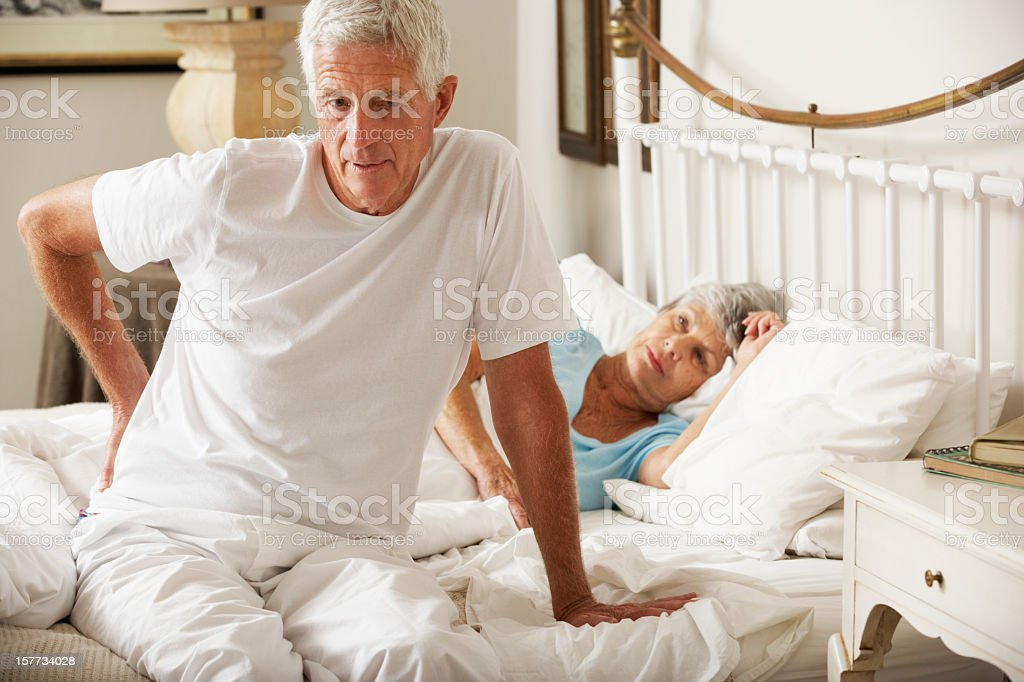 Senior Man Suffering From Backache Getting Out Of Bed royalty-free stock photo