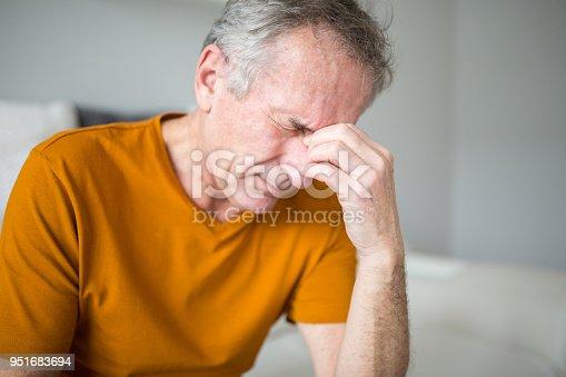 Portrait of senior man suffering from migraine