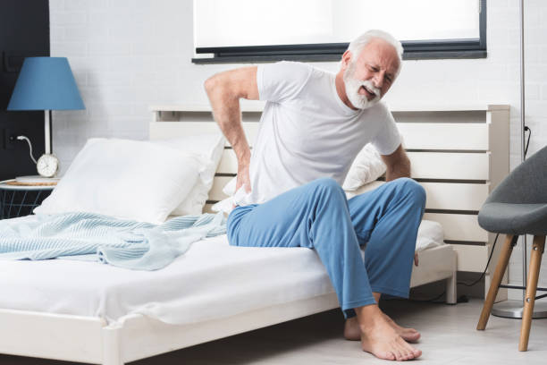 Senior man suffering from pain at home stock photo