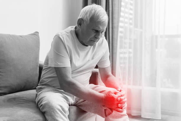 Senior man suffering from pain in his knee at home. stock photo