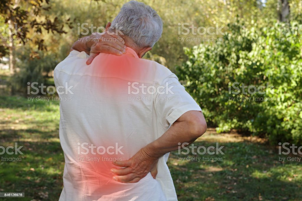 Senior man suffering fron back pain. Pain relief and health care concept. stock photo