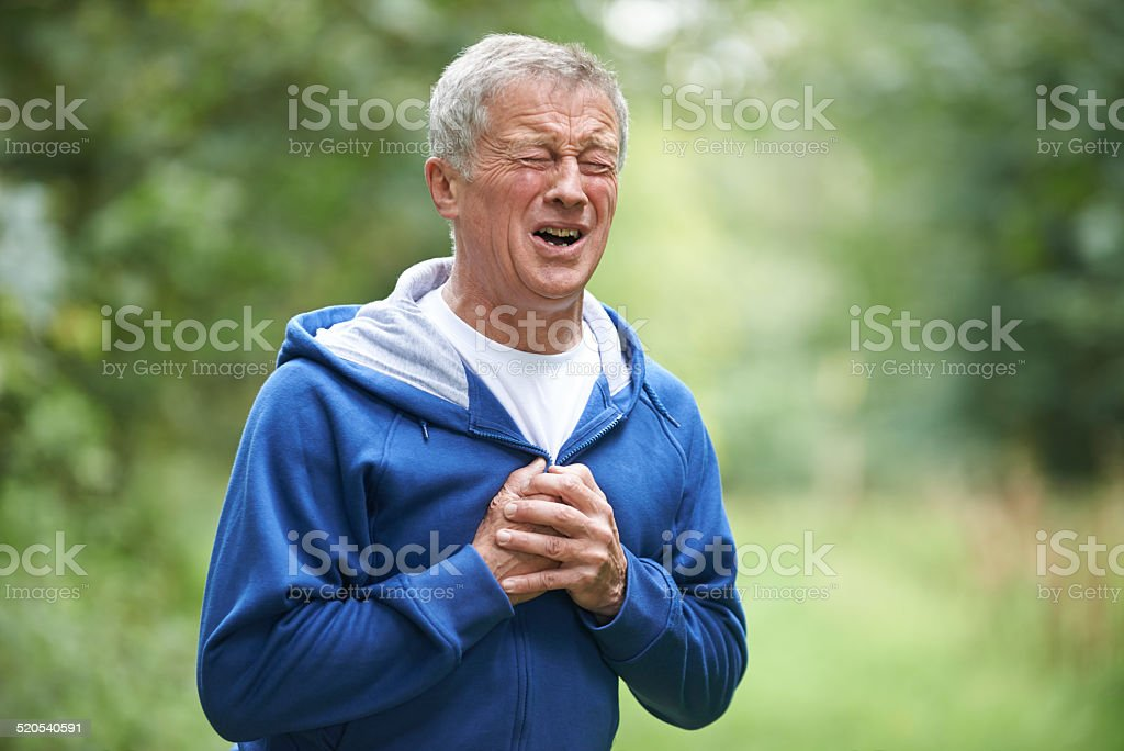 Senior Man Suffering Heart Attack Whilst Jogging stock photo