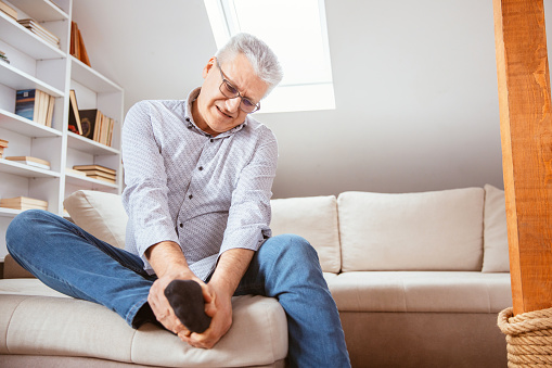 Senior man suffering with foot cramp on sofa in living room at home.