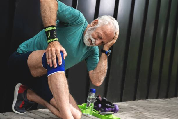 Senior man suffering with knee pain during workout stock photo