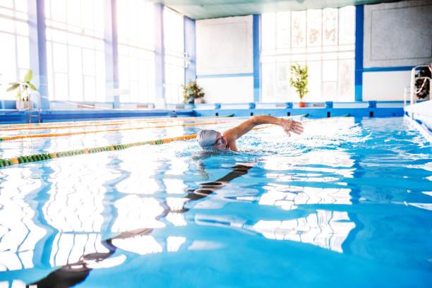 último homem nadar em uma piscina interior. - comodidades para lazer - fotografias e filmes do acervo