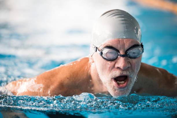 Senior man swimming in an indoor swimming pool. stock photo