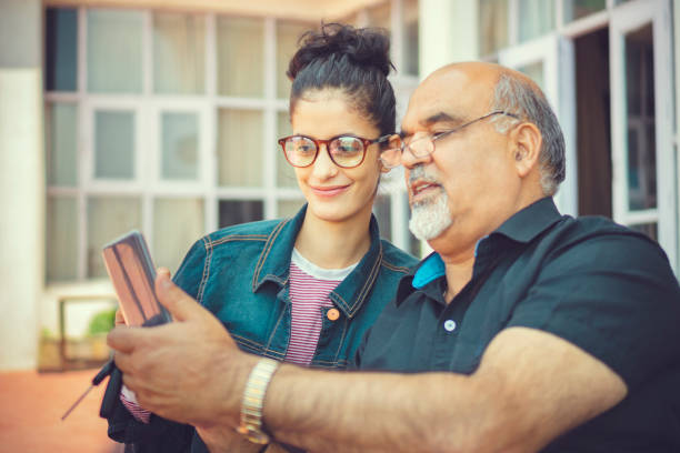 Senior man takes help in smartphone from a young woman. stock photo