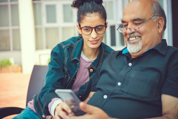 Seniorenmann nimmt Hilfe beim Smartphone von einer jungen Frau – Foto